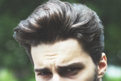 brunette man wears quiff with best hair wax