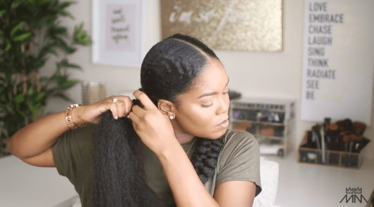 mini marley attaches extensions onto her braided hairstyle