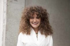woman with voluminous curly hair and bangs hairstyle