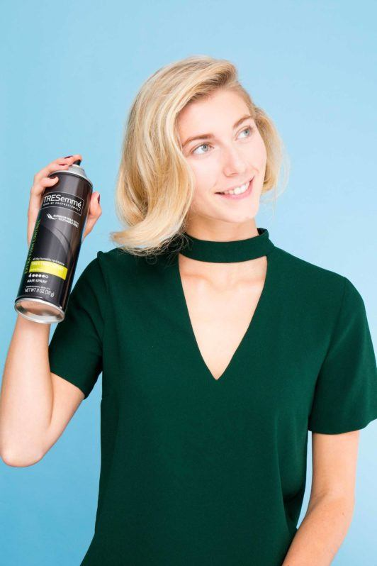 blonde woman applying hairspray