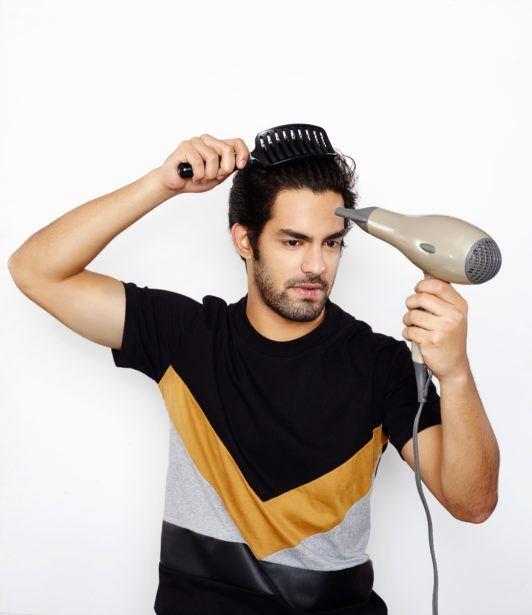 man blowdrying hair with brush