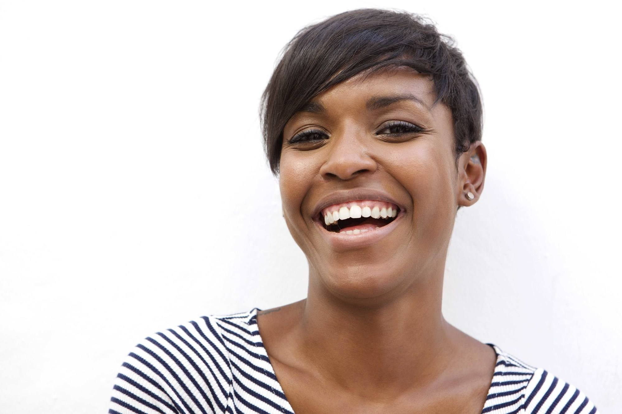 Close up portrait of a beautiful african american woman laughing on white background limit heat usage
