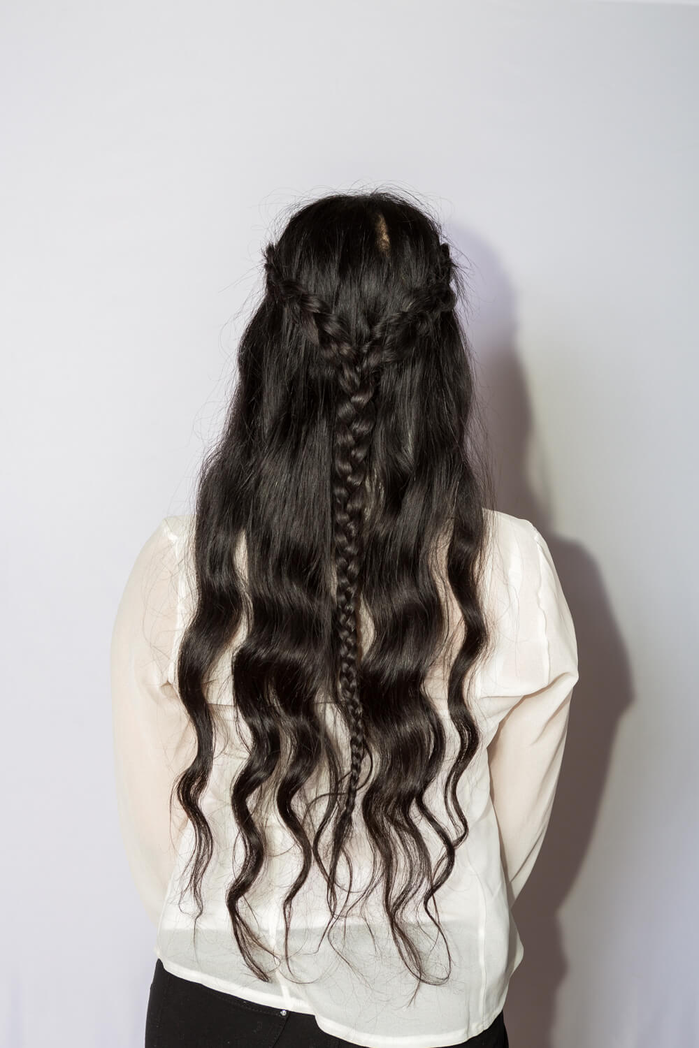 Brunette woman with natural waves wearing braided style
