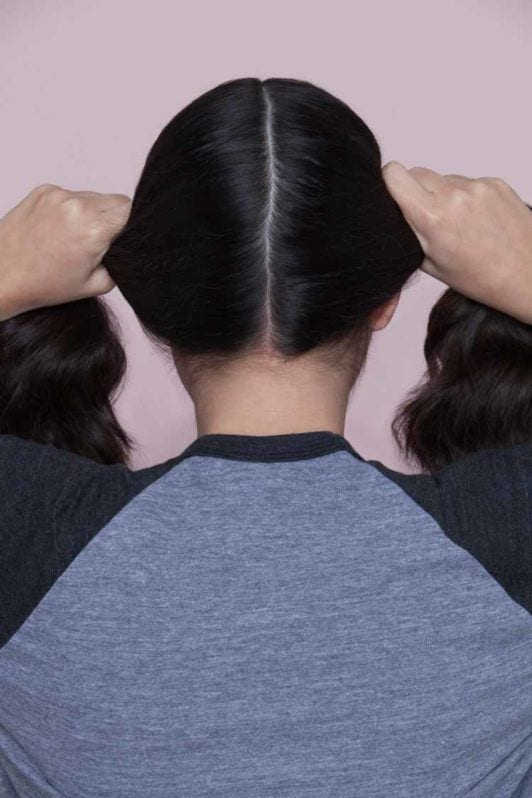 woman creating pigtails on her hair