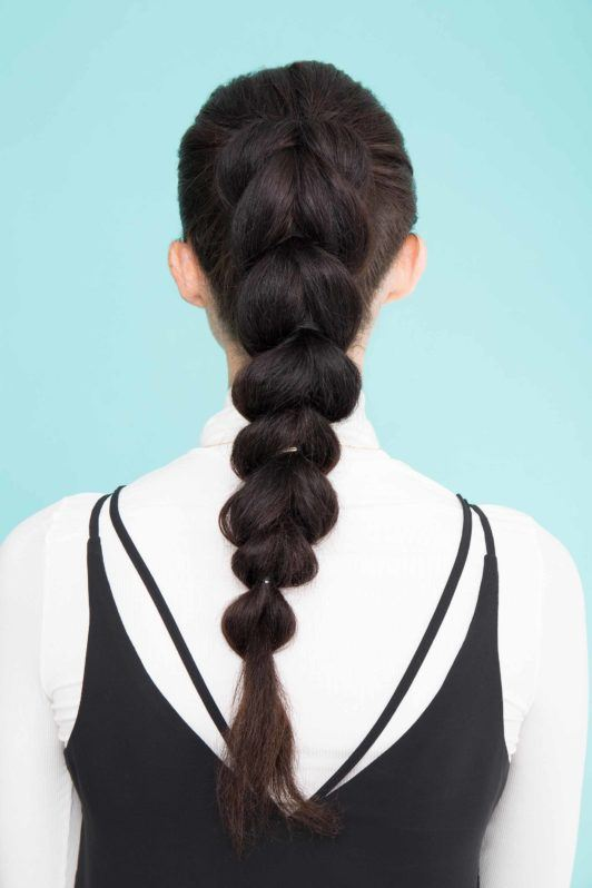 young lady with long black hair in pull through ponytail hairstyle