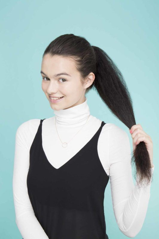 young lady with long black hair creating ponytail