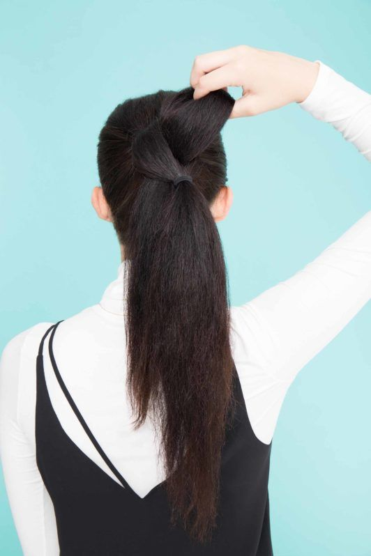young lady with long black hair pulling hair through ponytail