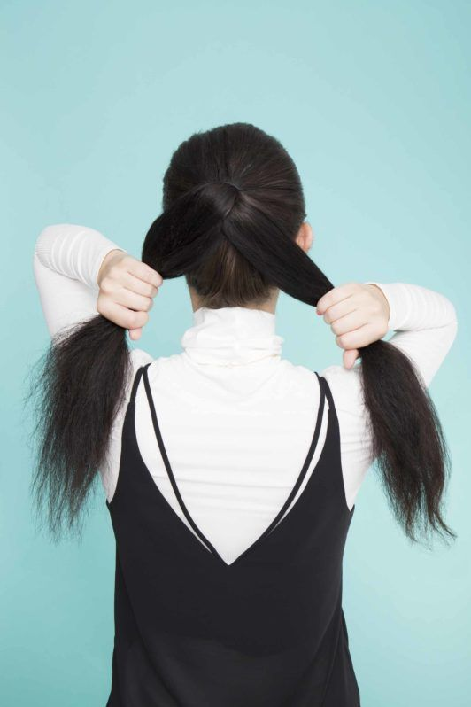 young lady with long black hair splitting ponytail