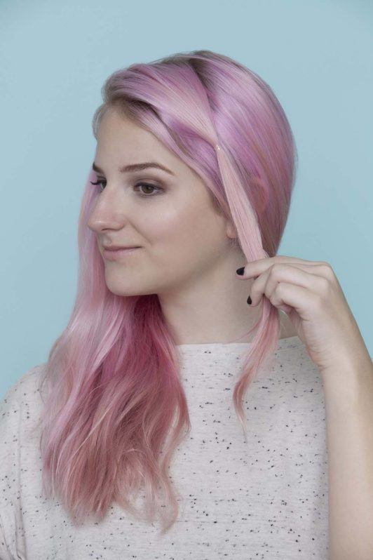 young woman with pink hair adding clear elastic band on her hair
