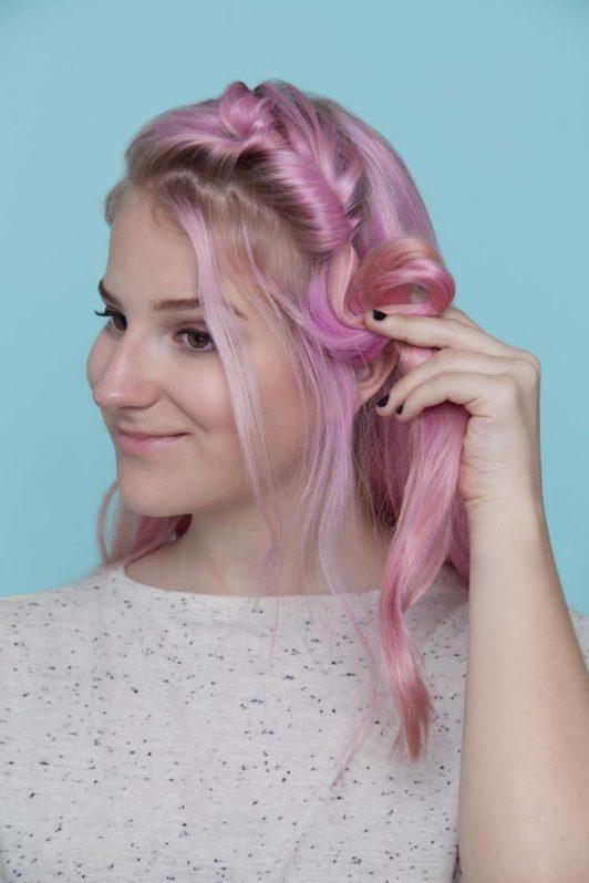 young woman with pink hair creating loops for pull through hair crown hairstyle