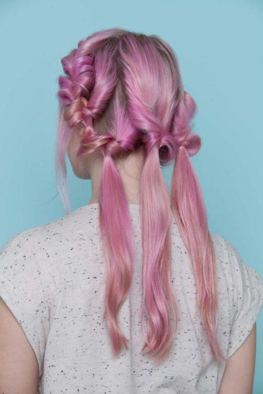 young woman with pink hair showing back view of pull through hair crown style