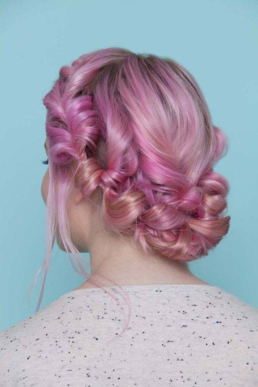 young woman with pink hair showing back view of pull through hair crown hairstyle