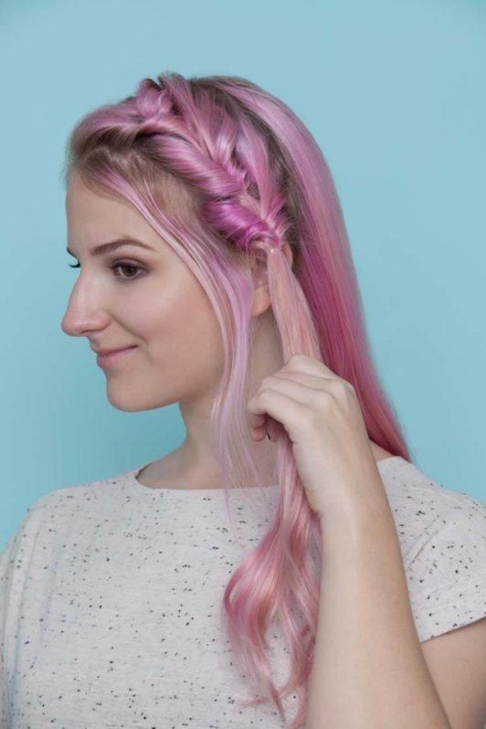 young woman with pink hair holding the ends of her hair