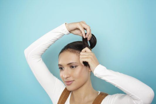 young woman creating space buns on her hair
