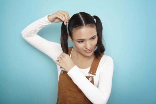 young woman creating pigtails on hair