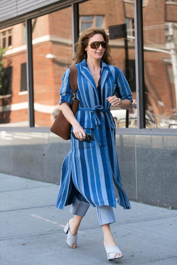 a woman wearing blue dress and denim wallking on the street