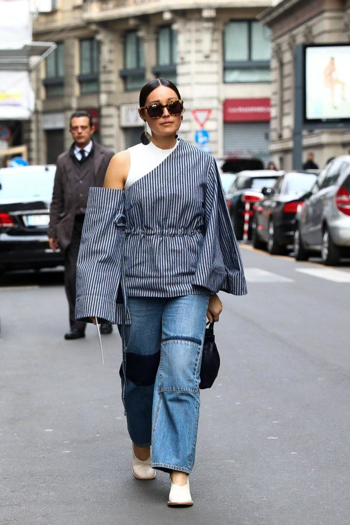 a woman wearing denim outfits with slickback bun walking on the street