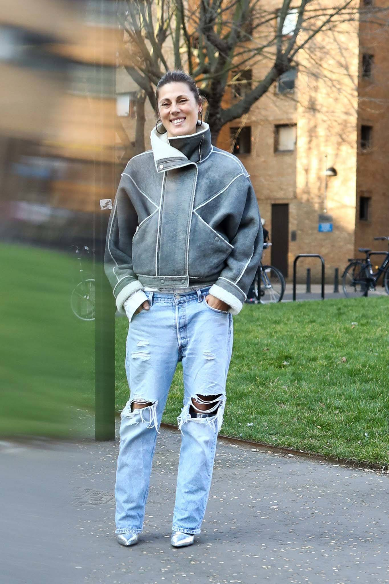a woman standing in a city park wearing a denim outfits and a coat