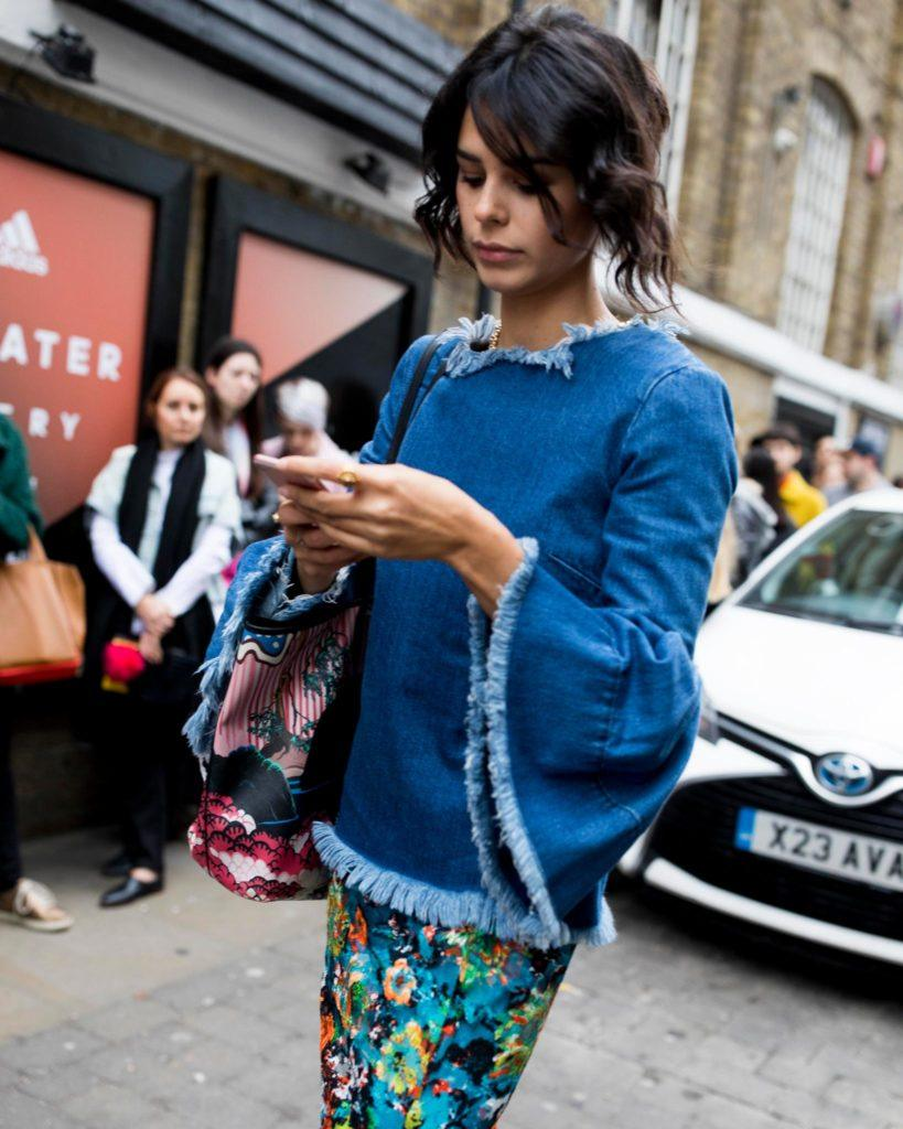 a woman walking on the street while checking her phone wearing blue denim outfits and floral skirts