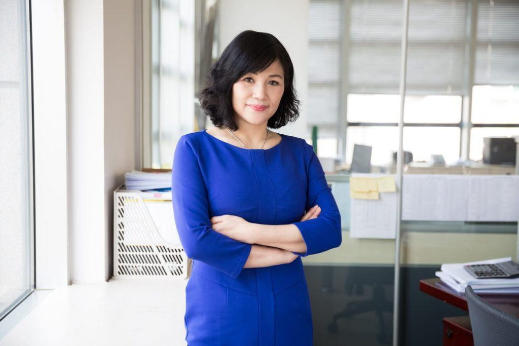 Woman with blue-black hair curly bob