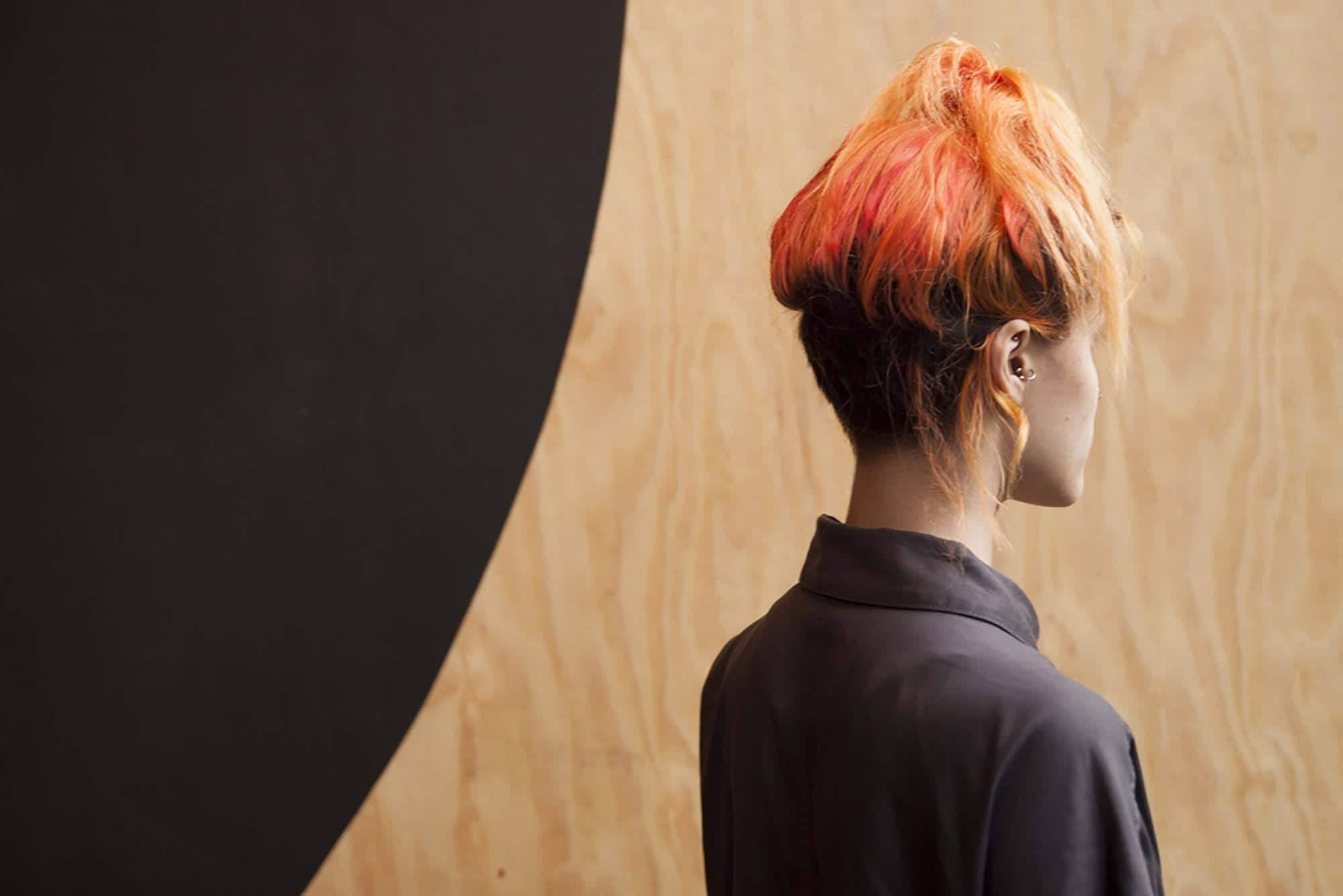 Beautiful women with blood orange hair worn in a high ponytail