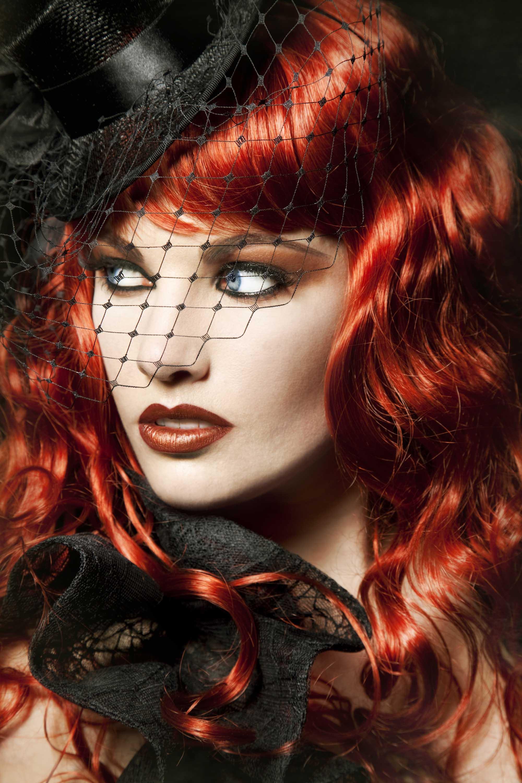 Beautiful women with blood orange hair worn in vintage waves