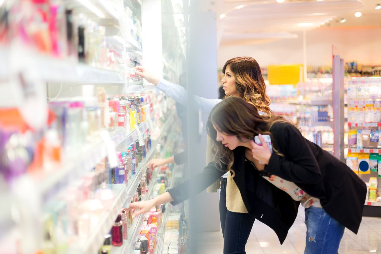 Two young women choosing products in a beauty shop budget-friendly must-haves