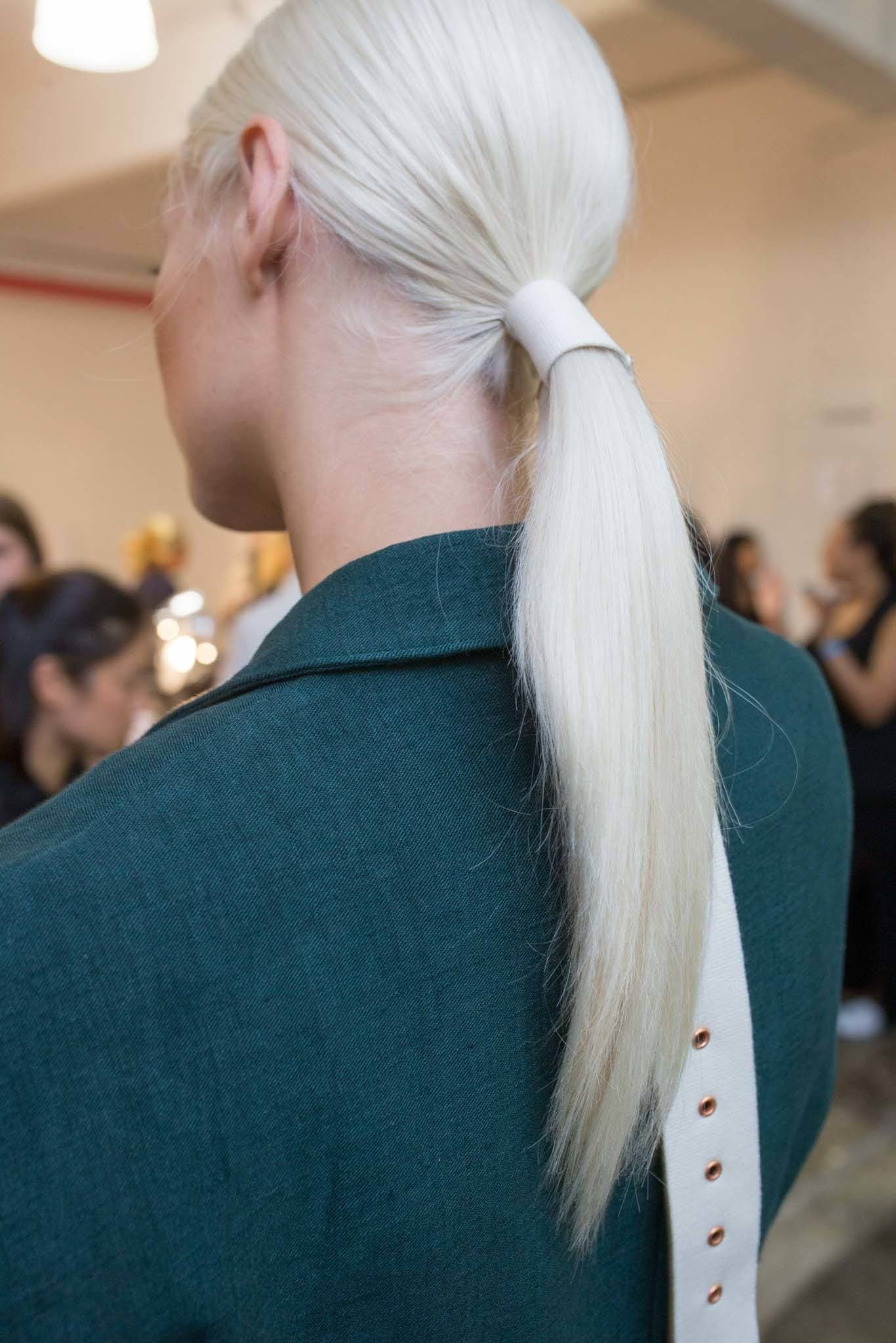 young woman with bleach blonde hair wearing belt on ponytail