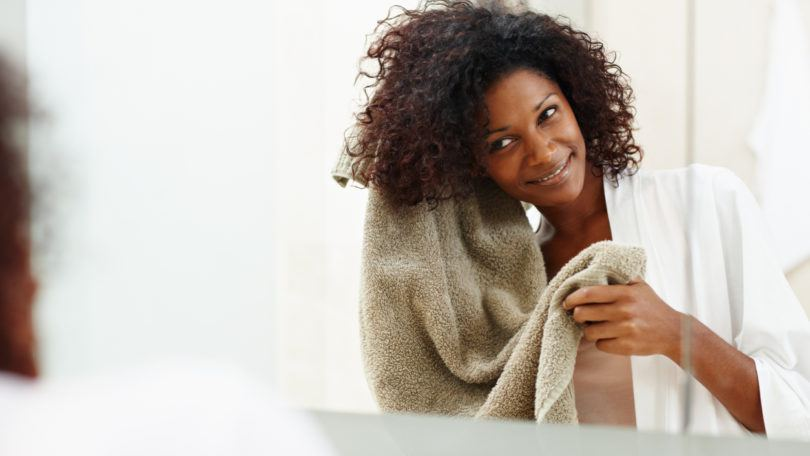 Beautiful african woman drying her hair with a towel in the mirror scalp scrub for hair