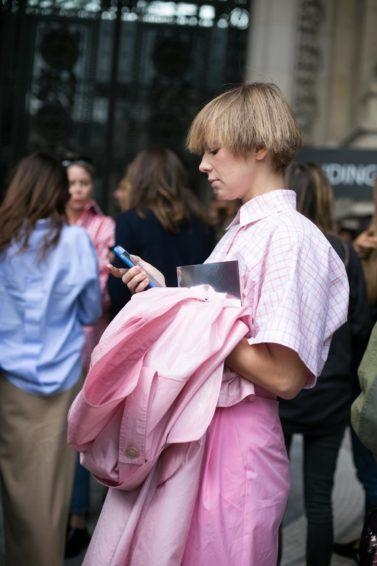 a woman with bob blonde hair wearing pink shirt