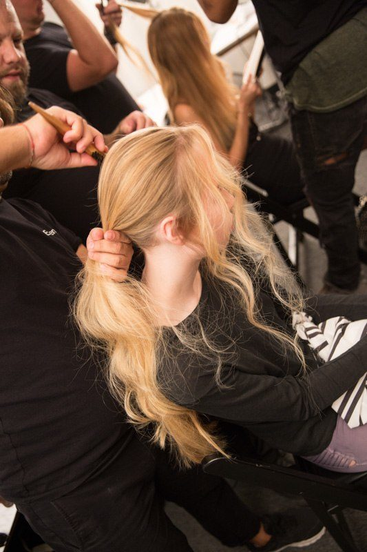 model getting hair styled into a messy ponytail backstage at nyfw