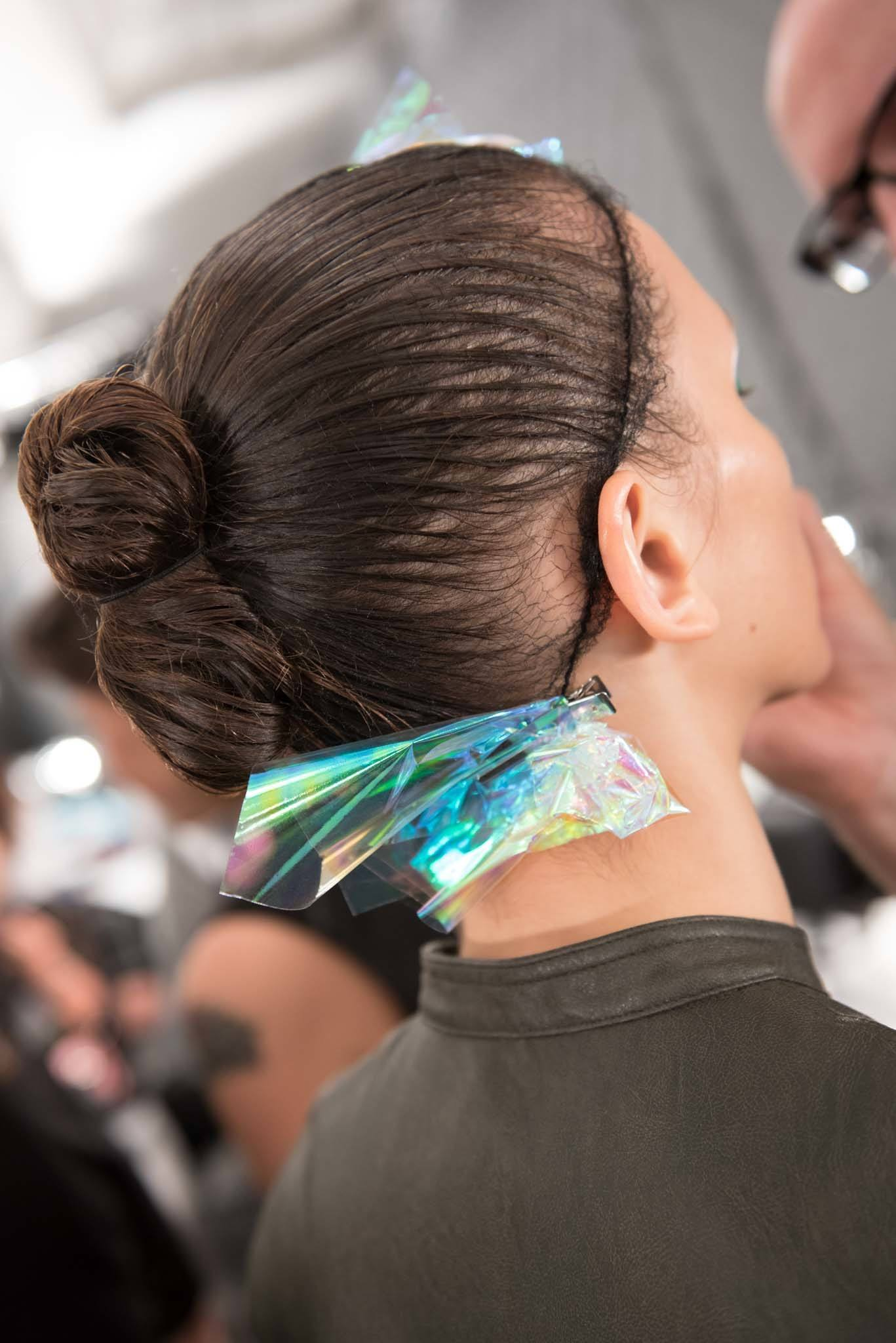 young woman with double top knot hairstyles backstage at fashion week