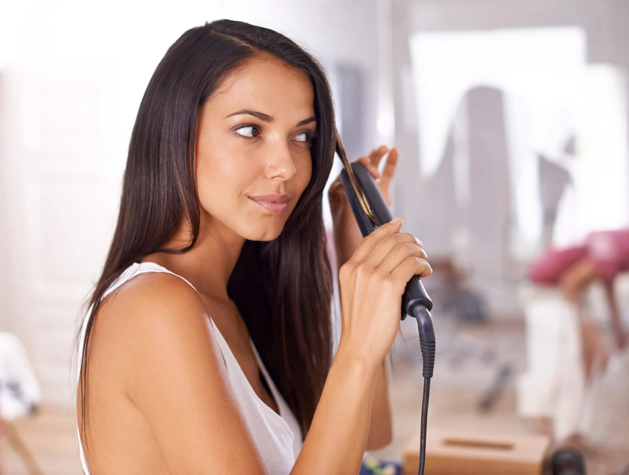 Woman with long hair flat ironing her hair.