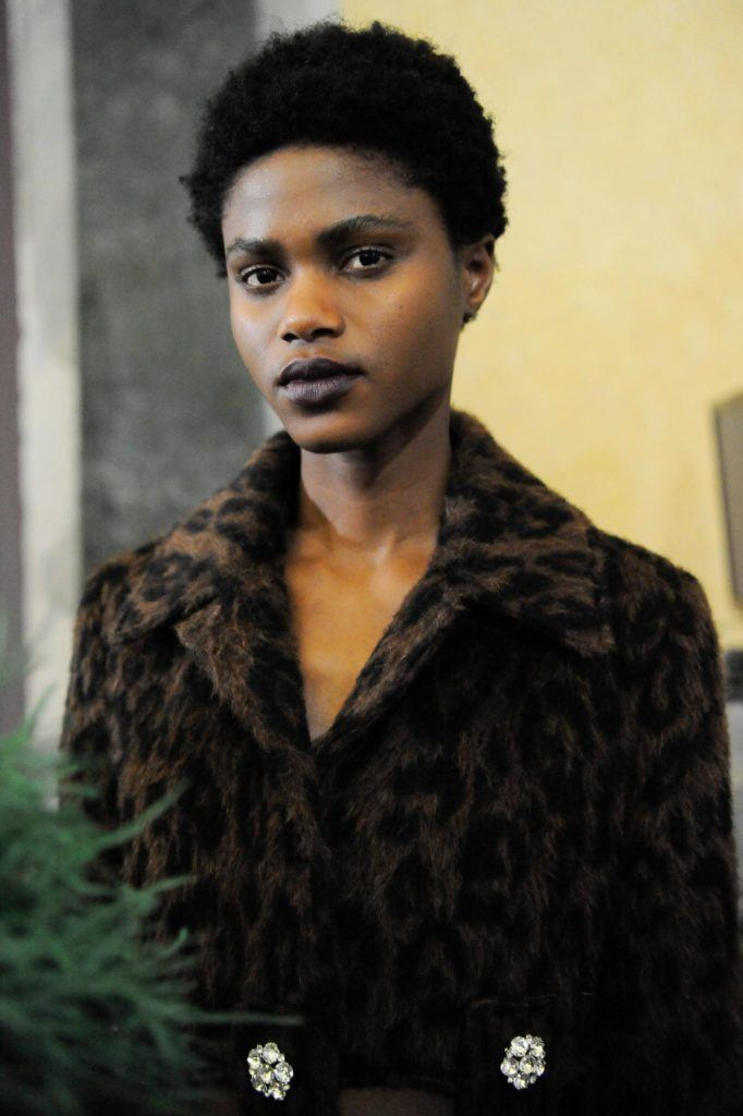 a female model with curly afro look wearing an animal print coat