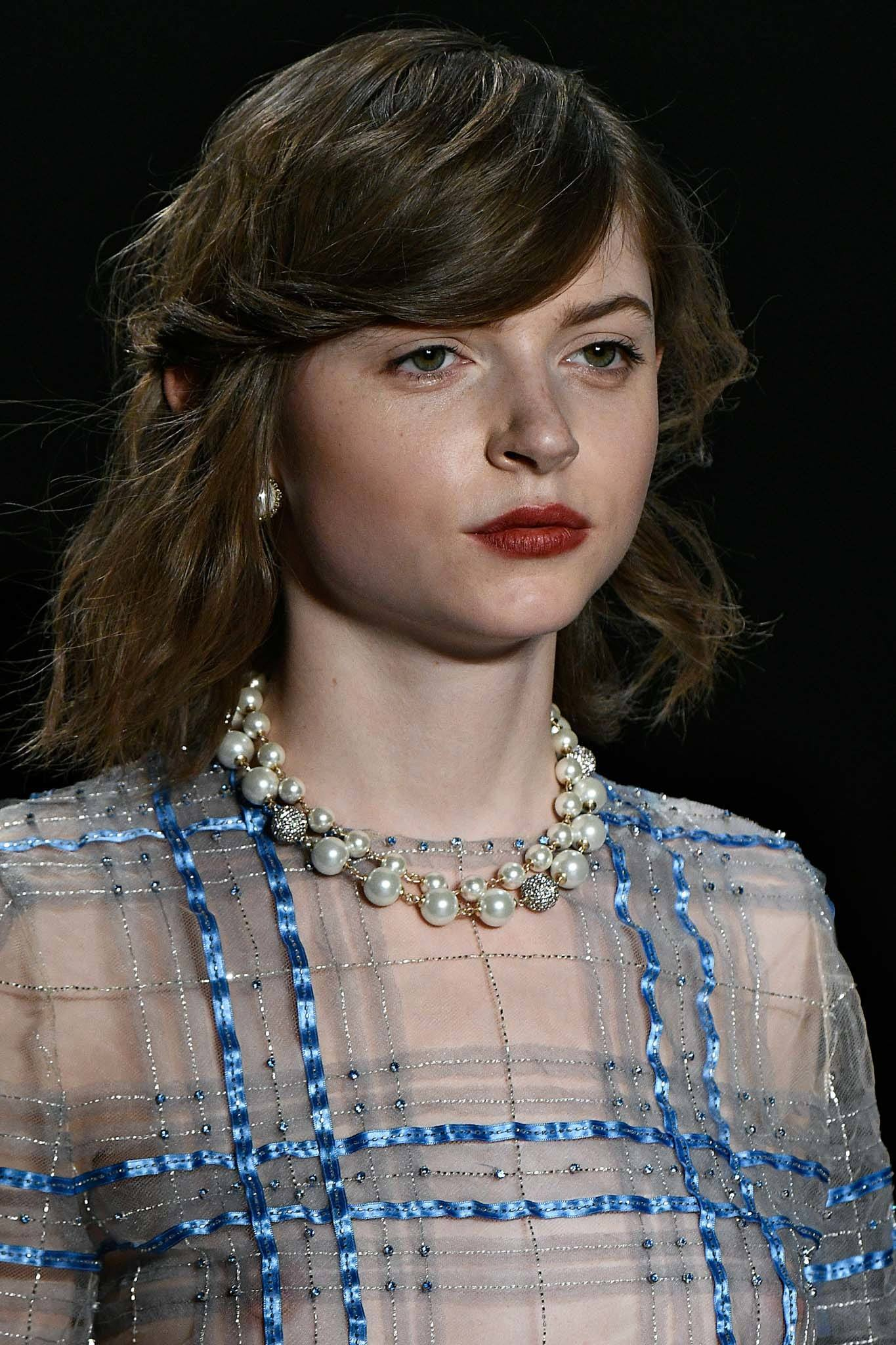 young model with side swept hairstyle with mussed-up texture.