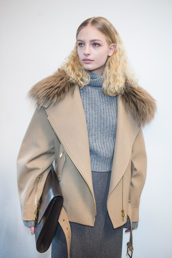 a blonde curly woman posing in a classy fur coat