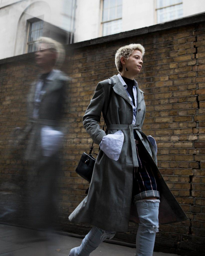a woman with high fade hairstyle walking on the street wearing a coat