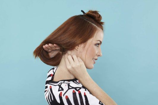 young woman with red hair creating wavy faux bob
