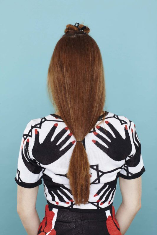 young woman with low ponytail on red hair
