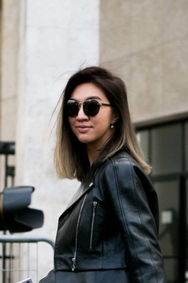 a woman walking on a street wearing leather black jacket and grey pants on