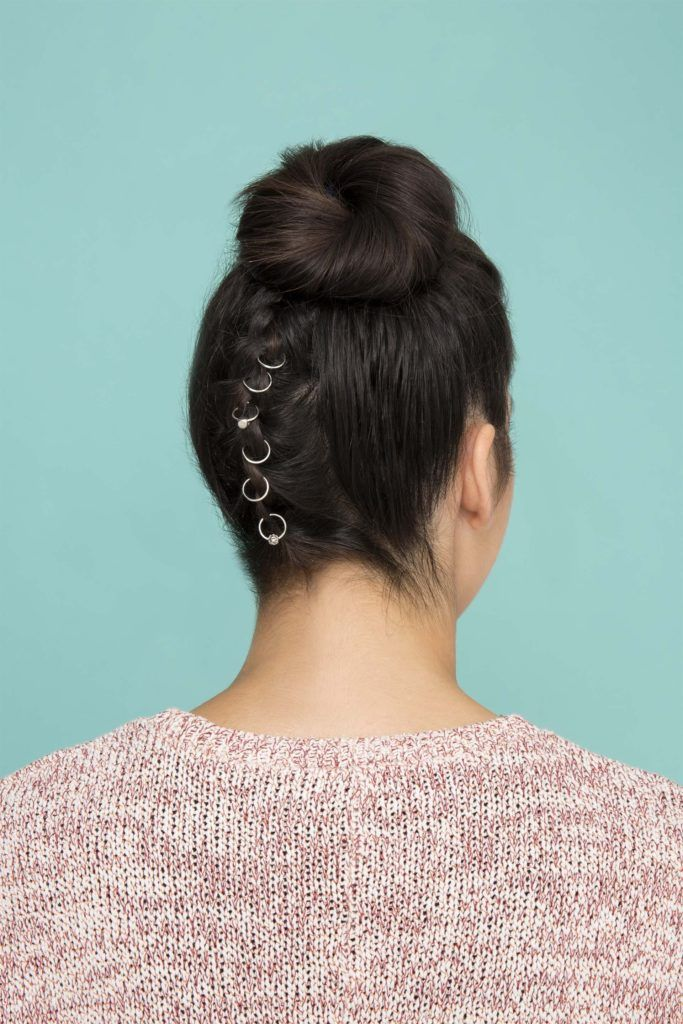 Woman wearing pierced festival braids in an updo.