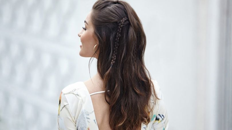 Woman wearing festival braids in a half updo.