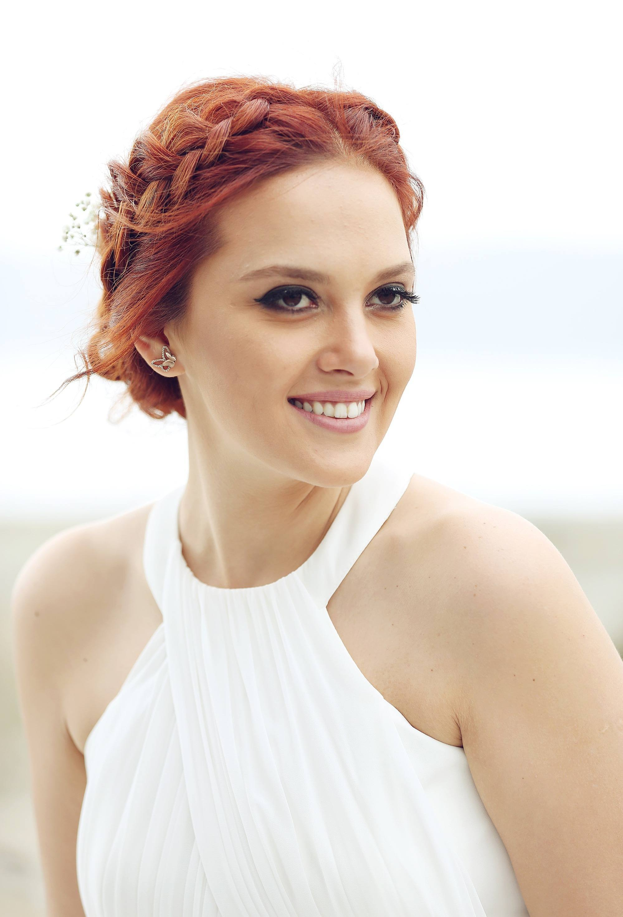 woman with red hair wearing middle part halo braid hairstyle