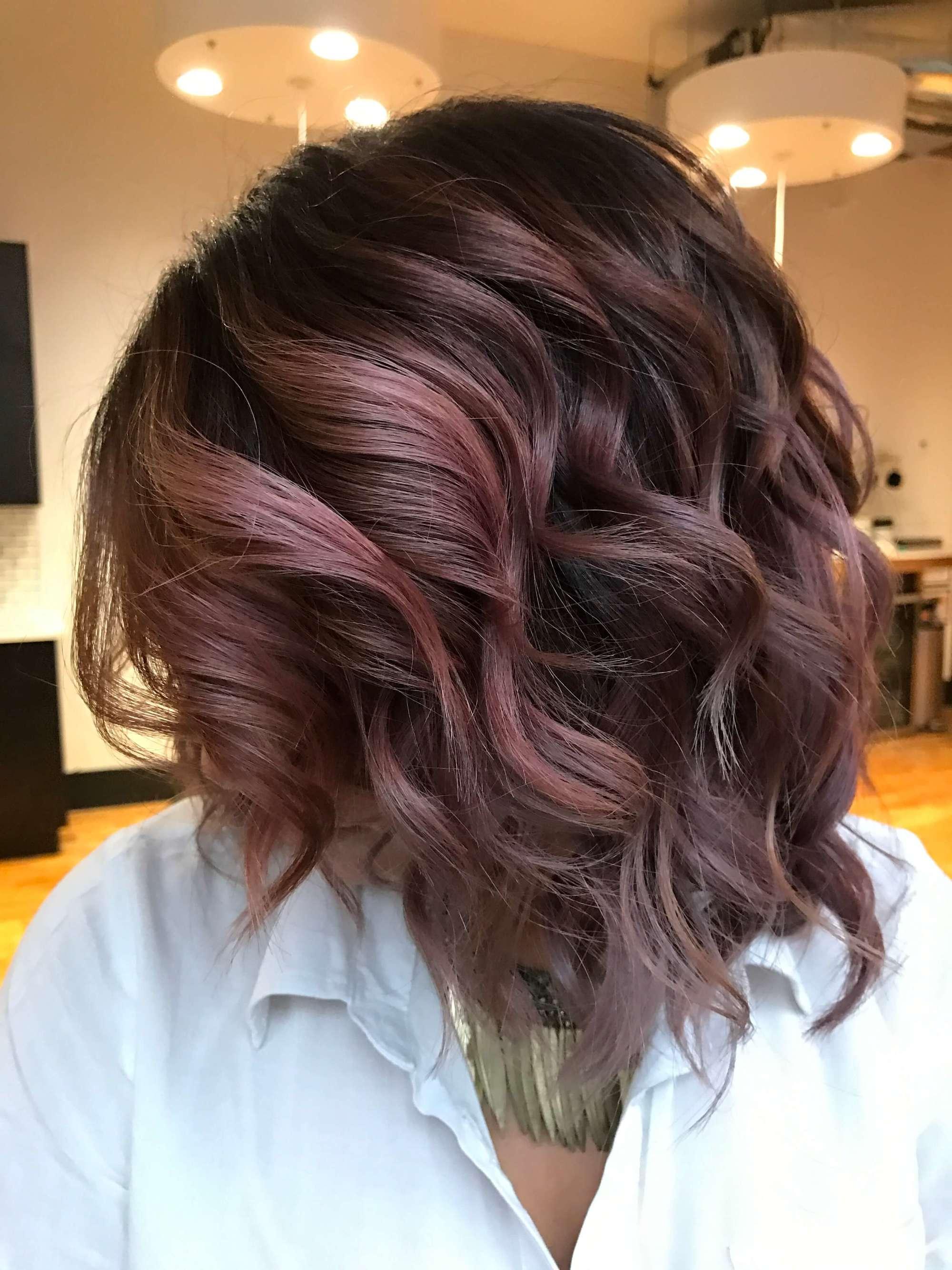 Woman with mauve hair streaks in brown hair.