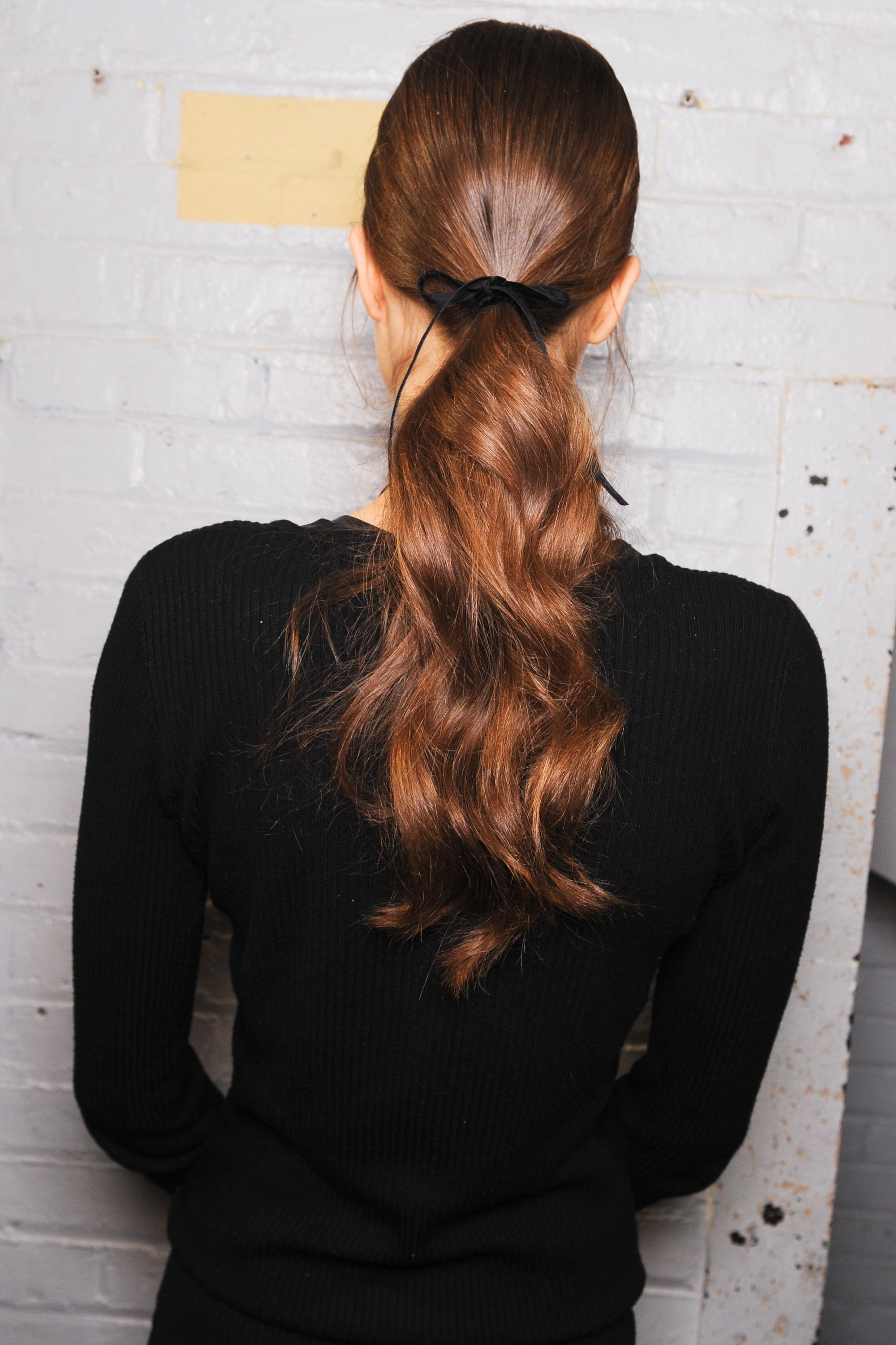 ribbon hair accessory trend with a curly ponytail