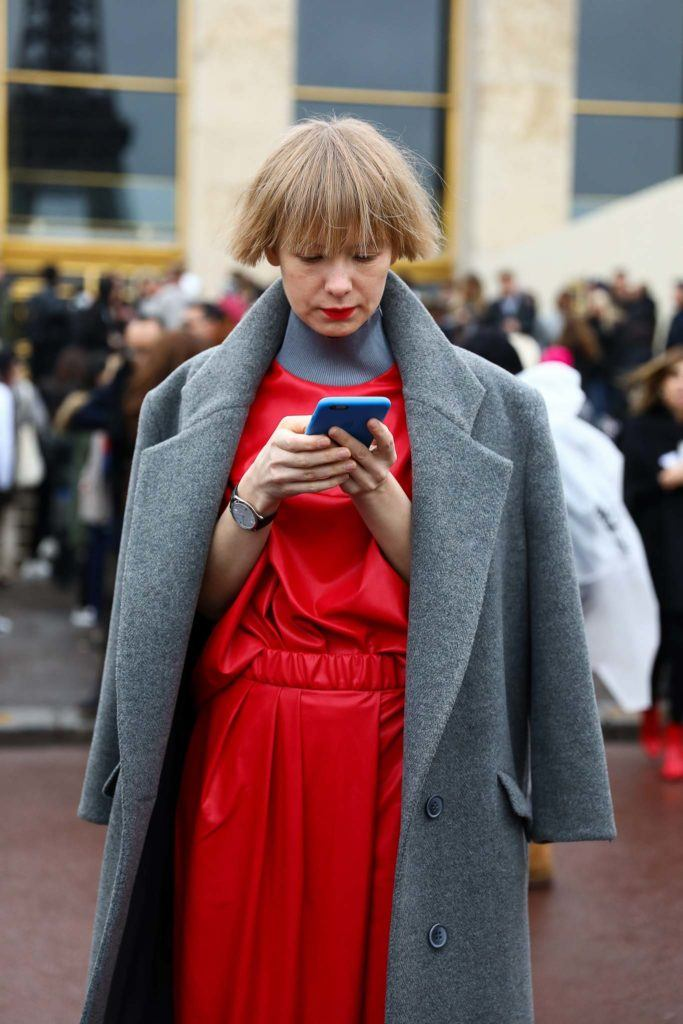 a fizzy blonde hair woman wearing a red dress and a coat checking her phone outside