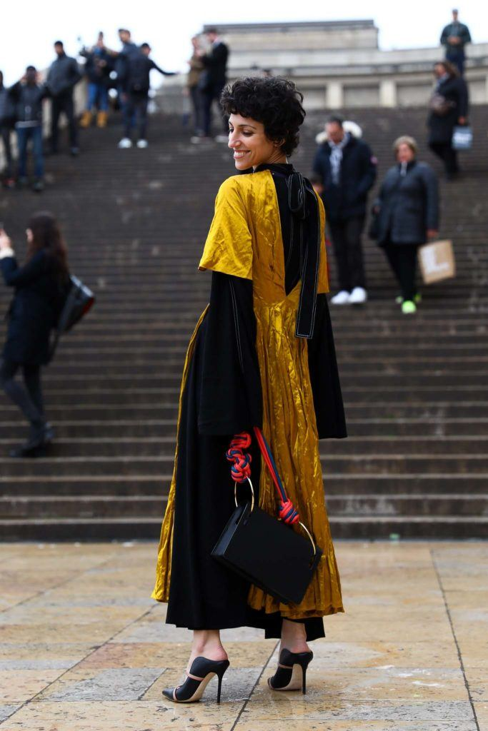 a short curly hair woman standing outisde and smiling to the people wearing black and yellow long dress