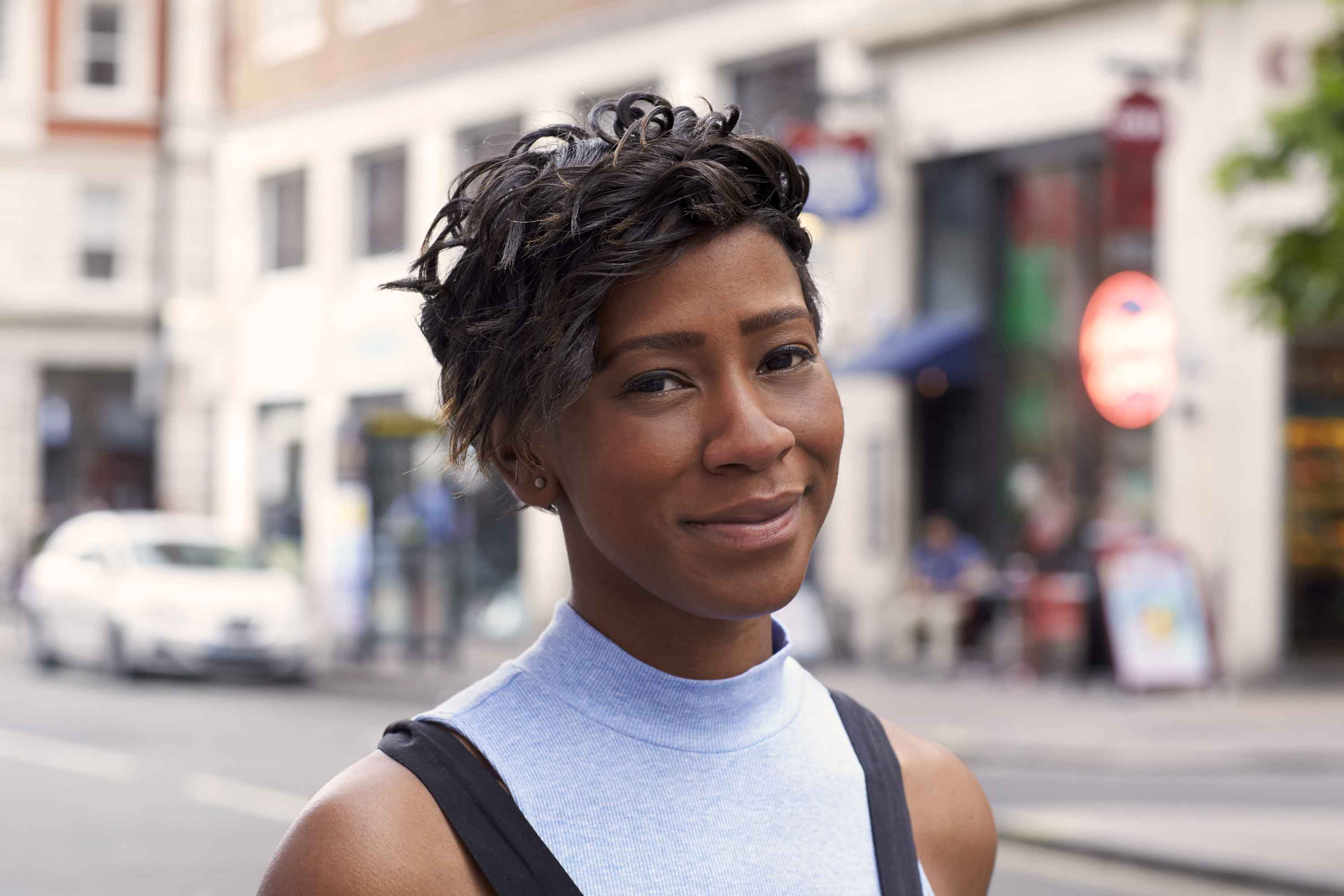 funky short hairstyles as shown by street style model with black curled hair