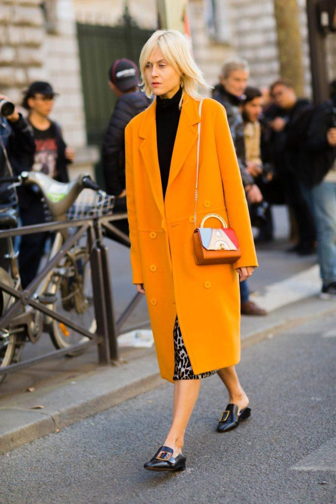 a short-straight blonde hair woman walking down the street wearing a bright yellow coat and an animal print dress