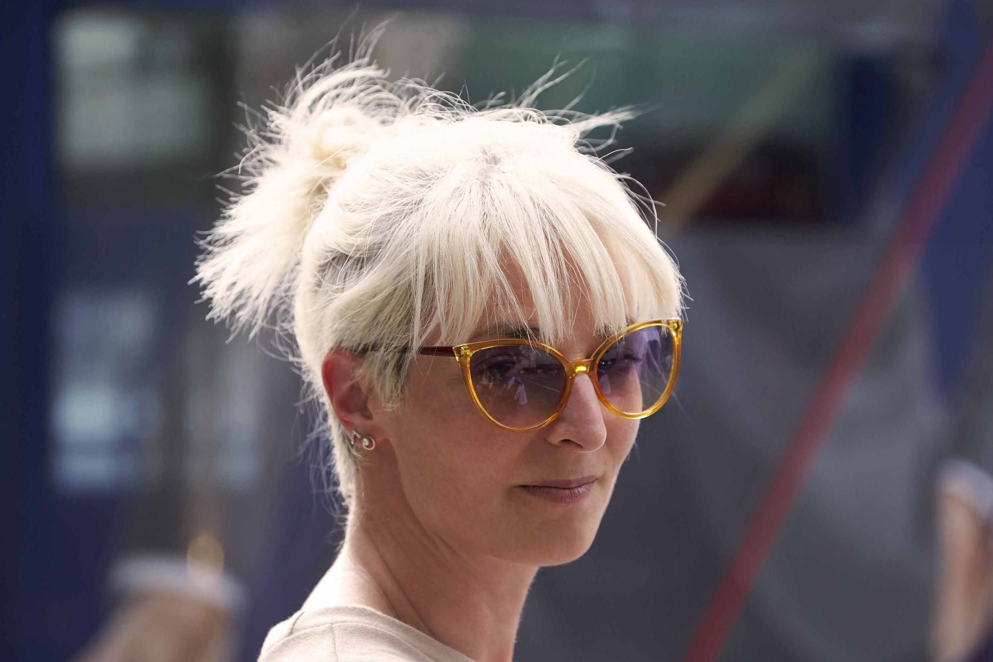 woman wearing messy bun on short platinum blonde hair